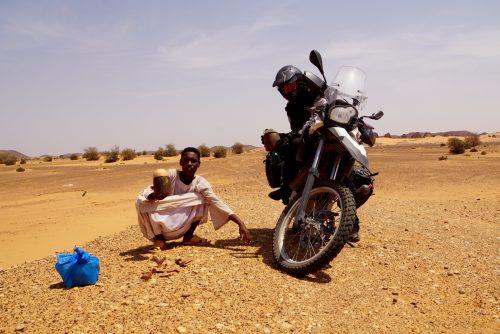 En lokal ung fyr solgte os en lerhøne lavet af hans mor. I baggrunden ses Meroe Pyramiderne.